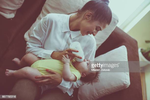 Mother and baby girl at home. Mother feeding her little baby.