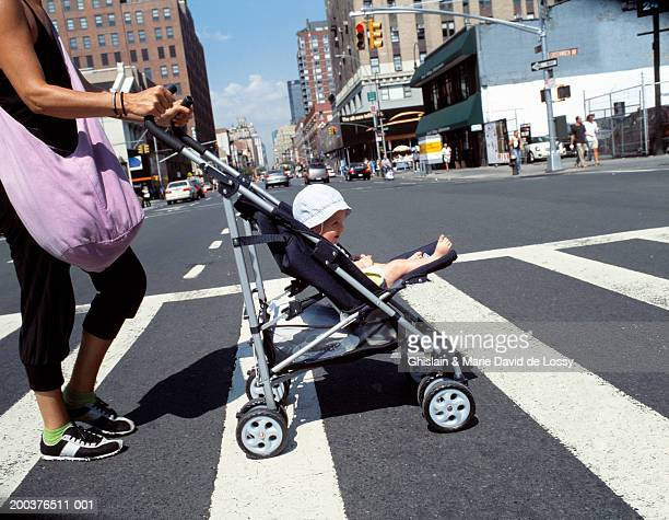 Mother and baby girl (9-12 months) in pram on pedestrian crossing
