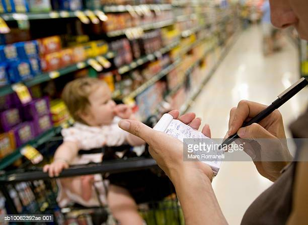 Mother and baby girl (9-12 months) in supermarket, focus on woman checking shopping list in foreground