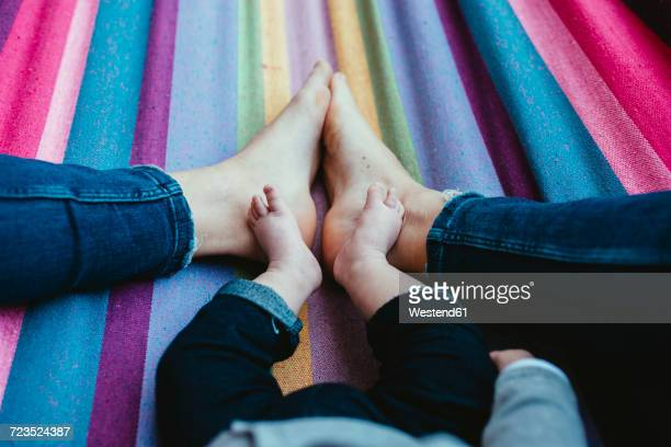 mother and baby girl lying barefoot on a hammock, partial view - big foot stock photos and pictures