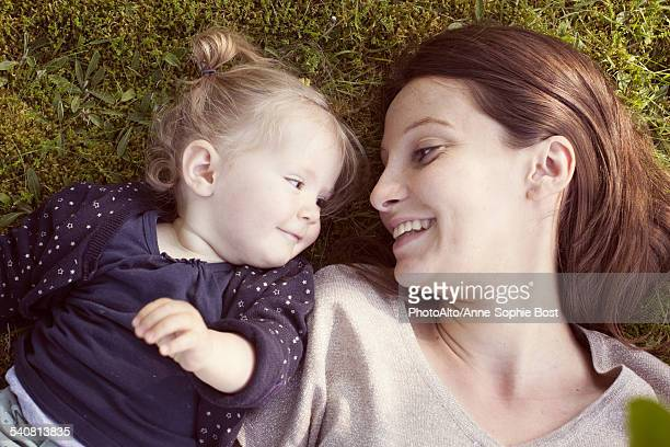 Mother and baby girl lying on grass, smiling at each other