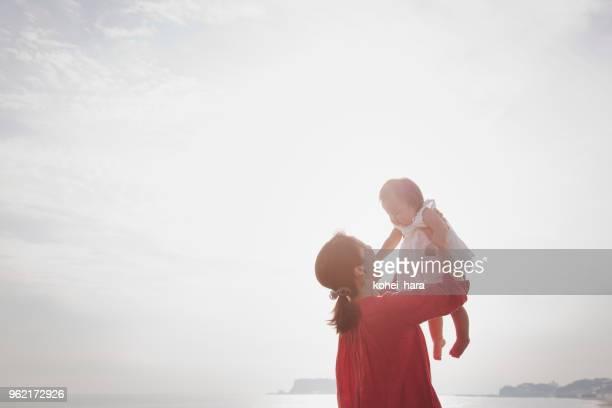 母と赤ちゃんの女の子が海辺でリラックス