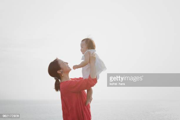 mother and baby girl relaxed at seaside - carrying stock pictures, royalty-free photos & images