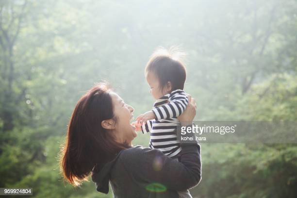 mother and baby girl relaxed in forest - japanese mom stock photos and pictures