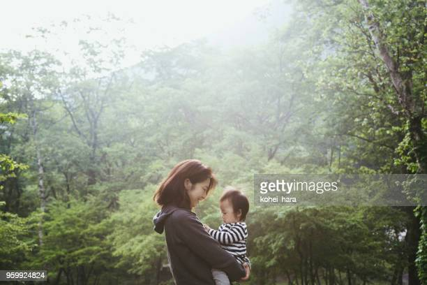 mother and baby girl relaxed in forest - simple living stock pictures, royalty-free photos & images