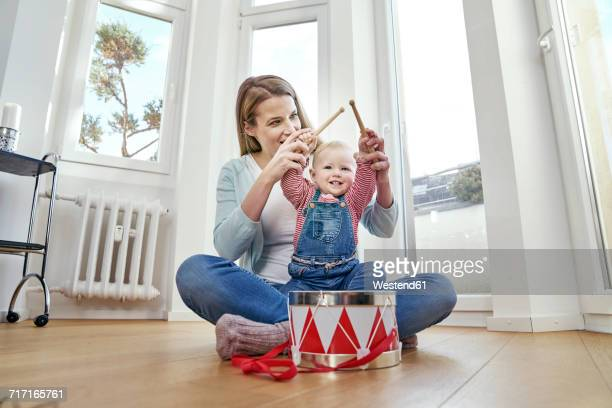 Mother and baby girl sitting on floor playing drums