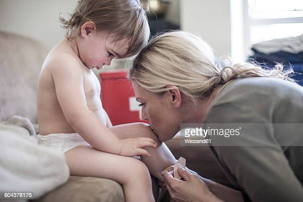 Mother and baby girl together at home putting on a plaster