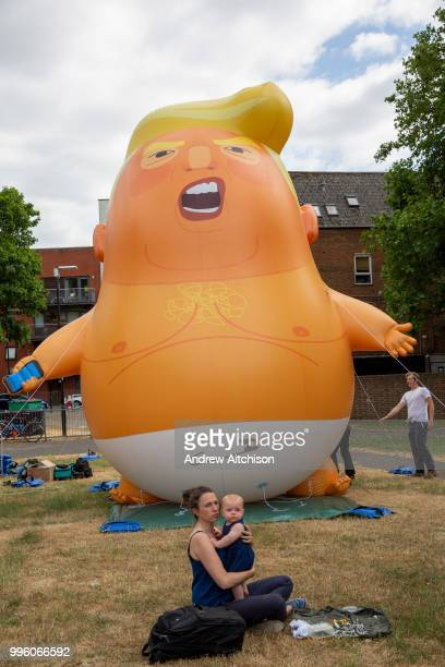 A mother and baby have a picnic in the part as the Trump Baby sitting team give the six metre high inflatable TrumpBaby his second London outing in...