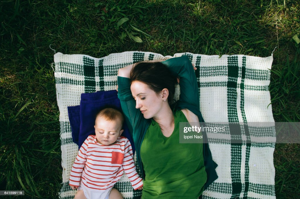 Mother and baby having a nap together on lawn : Stockfoto