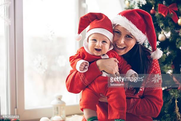 Mutter und baby im Weihnachtsmütze im the Christmas tree