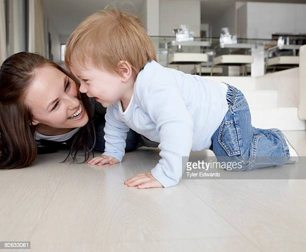Mother and baby laughing crawling on floor