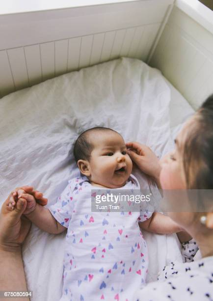 Mother and baby laughing on bed