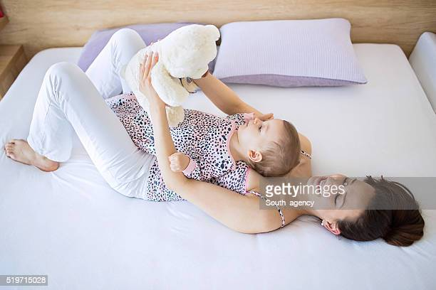 mother and baby lying in bedroom - mama bear stock photos and pictures