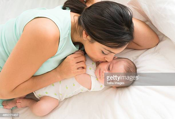 mother and baby (2-5 months) lying on bed - mexican and white baby stock photos and pictures