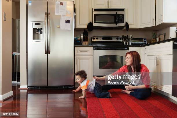 Mother and baby playing in kitchen