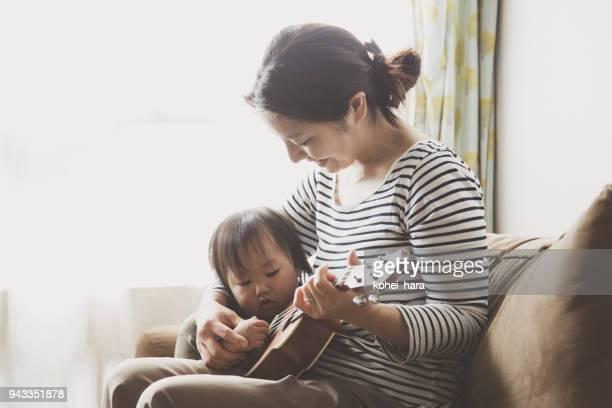 母子家庭でウクレレを演奏 - 趣味 ストックフォトと画像