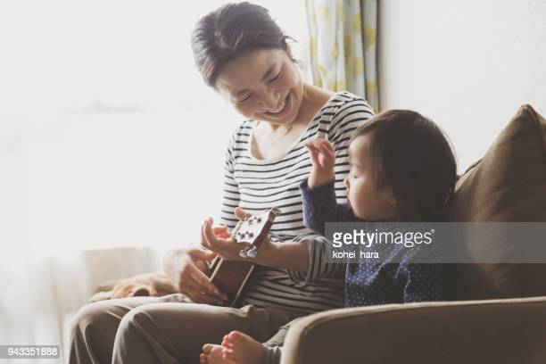 Mother and baby playing ukulele at home