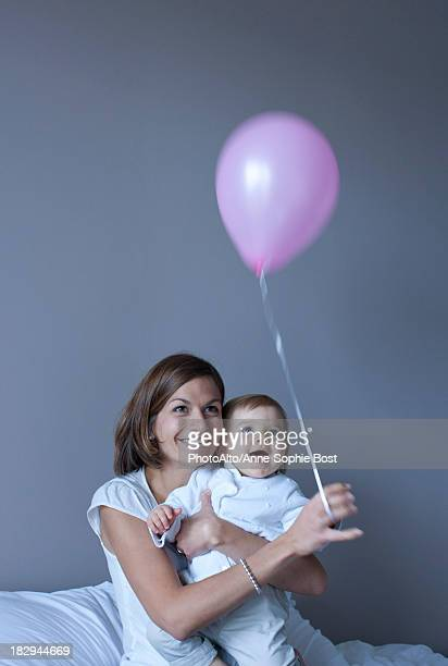 mother and baby playing with balloon - anne sophie mutter stock-fotos und bilder
