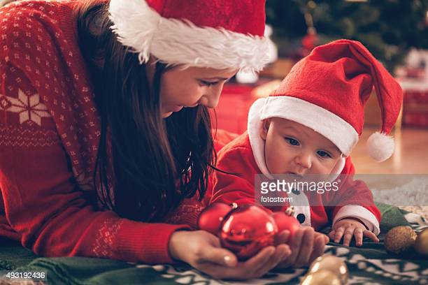 Mother and baby playing with Christmas ornaments