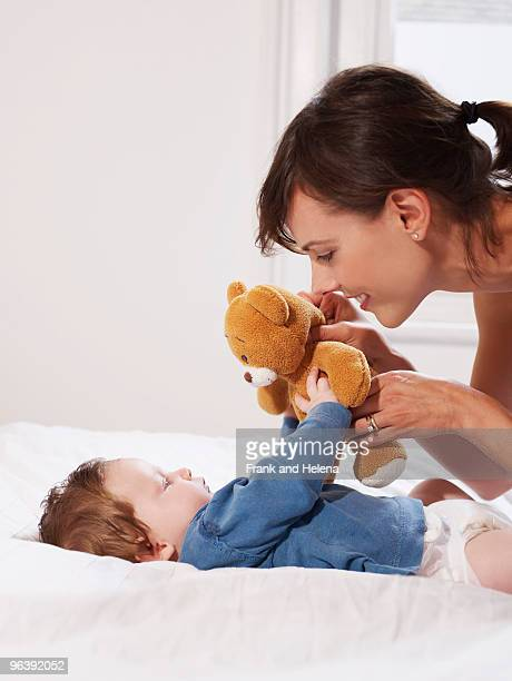 mother and baby playing with teddy bear - mama bear stock photos and pictures