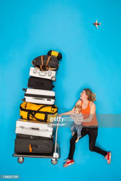 mother and baby pushing luggage trolley - toddler at airport stock pictures, royalty-free photos & images