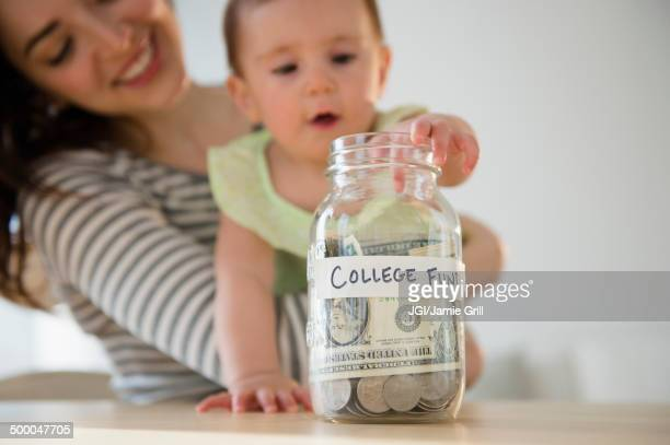 Mother and baby putting money in college fund