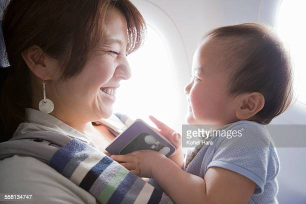 mother and baby reading a book on air plane