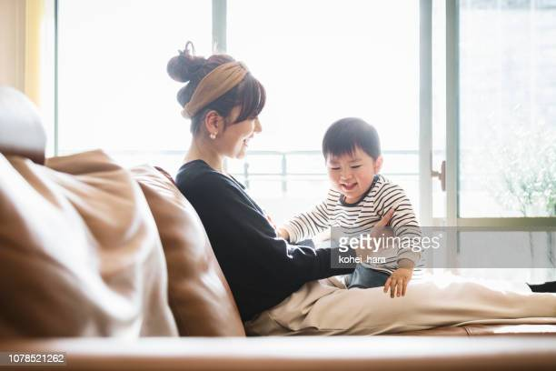 mother and baby relaxed on the sofa - childhood stock pictures, royalty-free photos & images