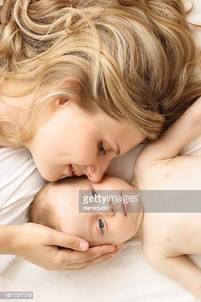 madre y bebé relaja en la cama - piel bonita mujer desnuda tumbada fotografías e imágenes de stock