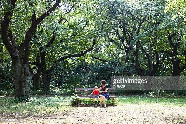 Mother and baby sit on bench in forest.