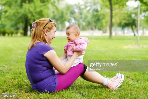 mother and baby sitting in park - ivanjekic stock pictures, royalty-free photos & images