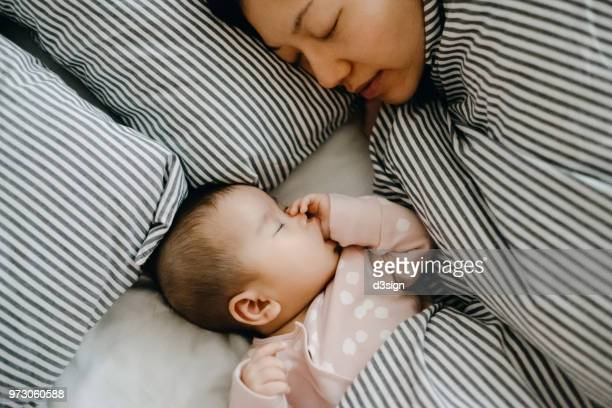 mother and baby sleeping in bed peacefully - lying on side stock pictures, royalty-free photos & images