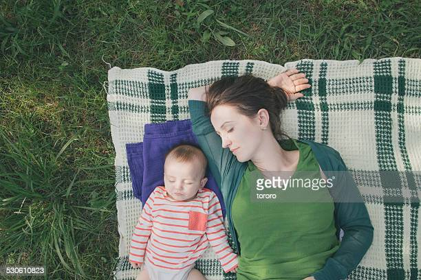 Mother and baby sleeping on blanket on grass