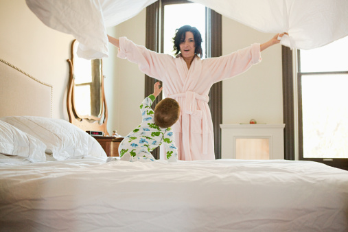 Mother and baby son making bed - gettyimageskorea