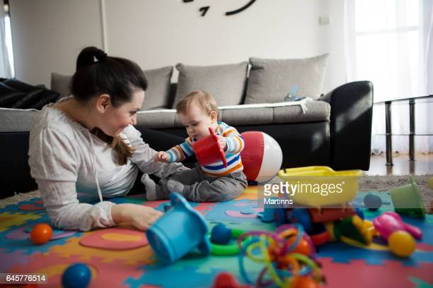 Mother and baby son playing in living room