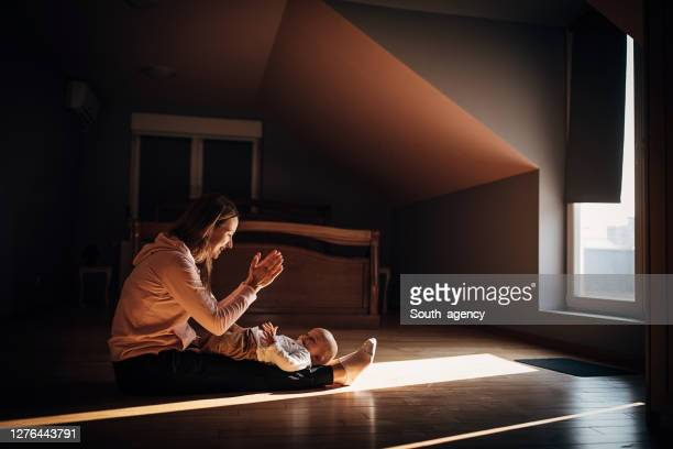 mother and baby son playing on the floor in bedroom - clapping hands stock pictures, royalty-free photos & images