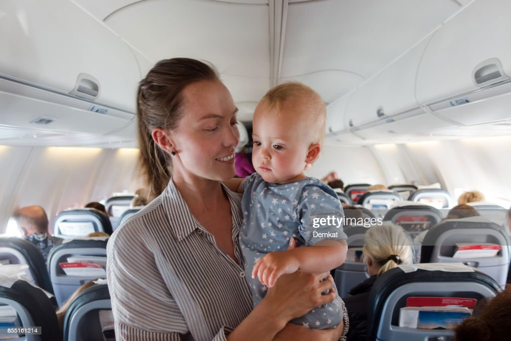 Mother and baby traveling on plane : Stock Photo