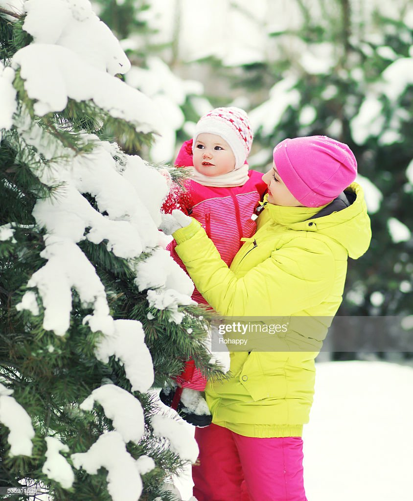 Mother and baby walking in snowy forest : Stock Photo