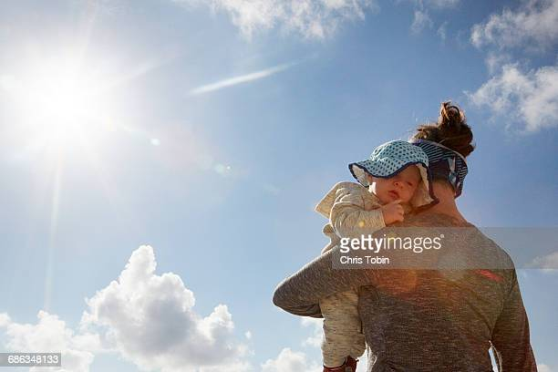mother and baby with blue sky and sun - sonnig stock-fotos und bilder