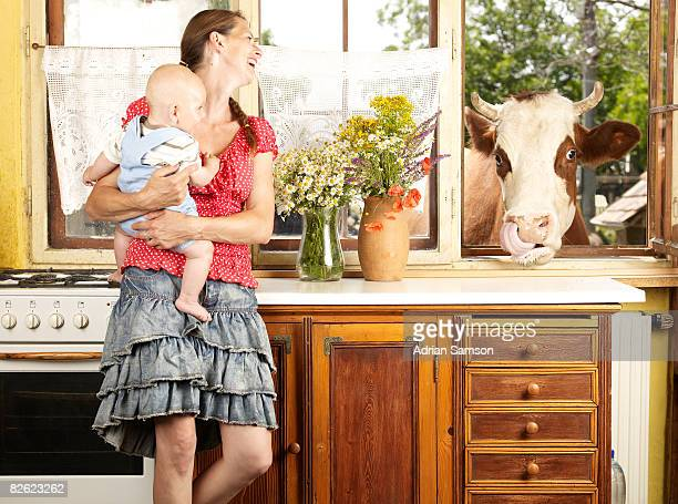 Mother and baby with cow looking through window