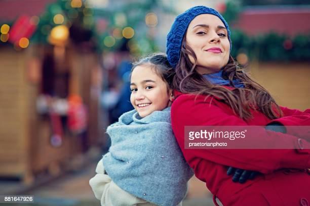 Moeder en geliefde dochter een rol spelen en plezier hebben op de kerstmarkt