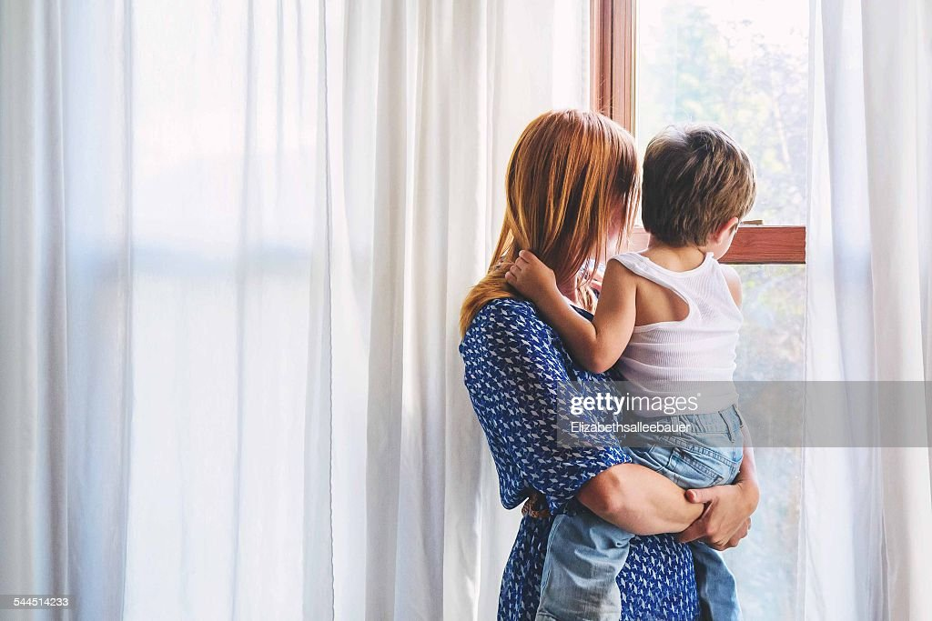 Mother and boy (2-3) child looking out of window : Stock Photo
