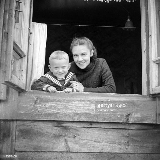 Mother and boy in open window of wooden house