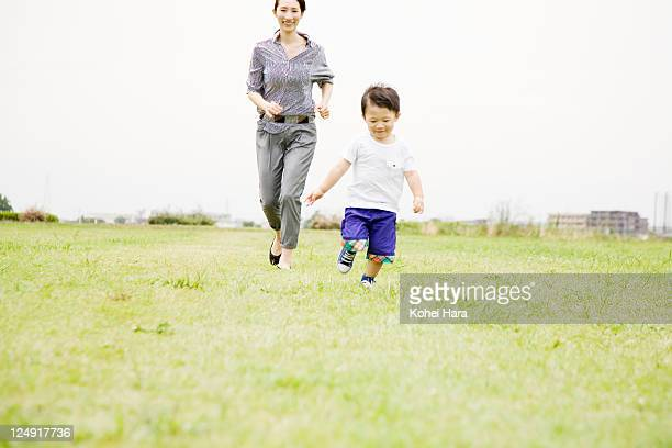 Mother and boy running on grass