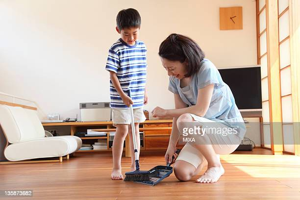 Mother and boy sweeping floor with broom and dustpan