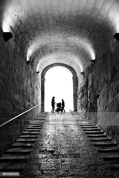 Mother And Boy With Baby Carriage Standing At Archway Of Tunnel