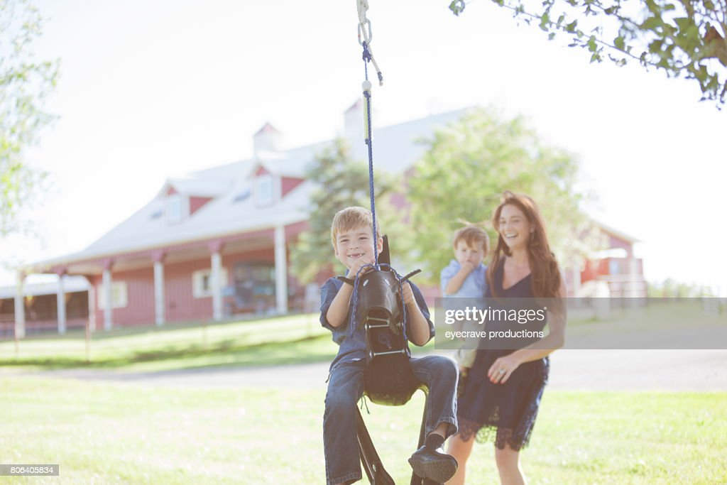 Mother and boys swinging on Rural Colorado Farm : Stock Photo