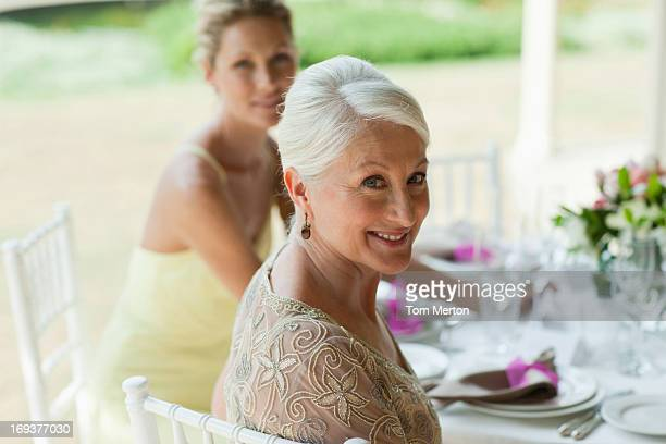 Mother and bride sitting at dining table