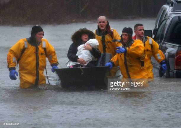 A mother and child are rescued by boat from their home in the Houghs Neck section of Quincy MA during a nor'easter storm on March 2 2018 Quincy...