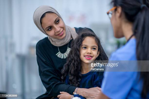 mother and child at doctor's office - refugee stock pictures, royalty-free photos & images